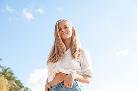 Beautiful young blonde girl with flowing hair and dimples against the blue sky and the sun, pretty smile