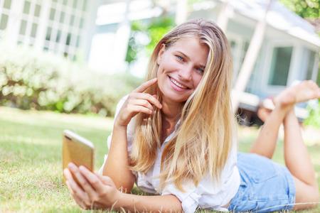 Mooi blond meisje, op een zomers groen gazon, met een smartphone in haar handen geniet van de zon van de zomer en de lente