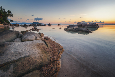 Sea sunset rocks beach on blue sky background. Beauty evening sunrise. Blue background. Sandy beach with rocks Stockfoto