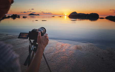 Photo camera on tripod on the beach at sea sunset. Hobby travel photography concept. Beautiful sea landscape Stockfoto