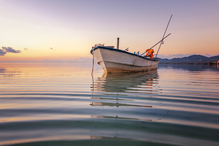 Blue sea at sunset, boat fishing  Shore landscape bay. Summer beautiful   scenery. Blue water. Stockfoto