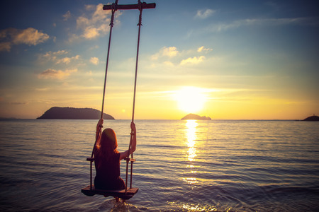 Young beautiful happy woman swinging on a swing on the beach during sunset, relaxing travel lifestyle concept