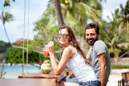 Young beautiful couple in love on the tropical sea, in beach cafe during a honeymoon holiday, Valentines Day. Love concept. Travel to the island
