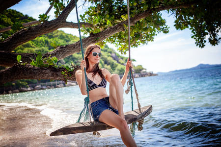 Young beautiful happy woman in top and shorts swinging on a swing on the shore of a tropical sea during vacation. Travel and vacation concept Stockfoto