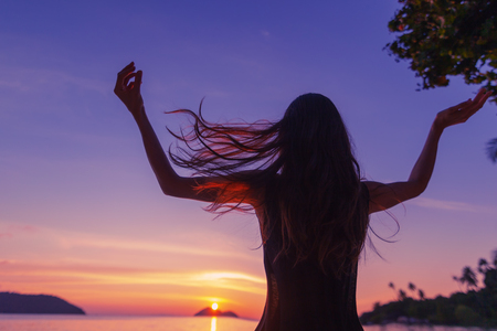 Silhouette of a beautiful slim young woman on a background of bright colorful sunset on a tropical beach