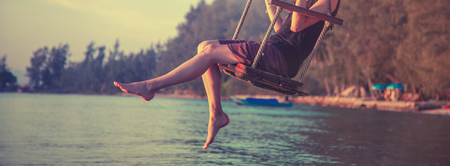 slender female legs close up, woman swinging on a swing on the beach during sunset, rest, travel, lifestyle concept