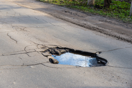 with holes: Road hole. Repair work grey asphalt puddle