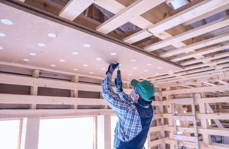 glasswool: Construction worker thermally insulating eco wooden frame house with wood fiber plates