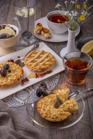 Breakfast for two, lemon tarte and tea on wooden table Stock Photo