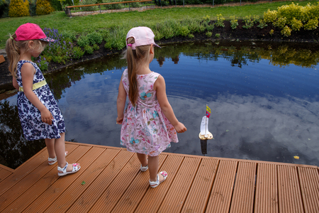 Duas meninas, lançar, um, barco brinquedo, em, um, lagoa, parque, latvia Foto de archivo - 82334952
