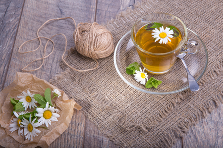 Cup of tea with chamomile flowers on rustic wooden background.