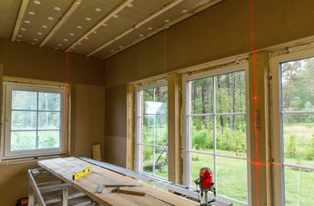 Construction work, finishing work in a wooden house and installing windows using the level of the laser line