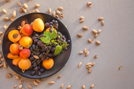 Fruit plate with grapes, apricot and almond on black plate