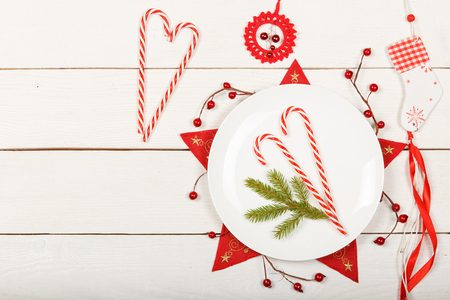 Christmas table setting with white dishware and red decorations on white wooden background. Top view. Copy space.
