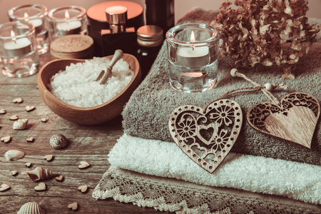 Spa concept in Valentines Day, candles, handmade heart, dry flower seashells, setting for aroma therapy and salt massage on bed, relax and healthy care. Rustic style. Toned image in chocolate, tones.