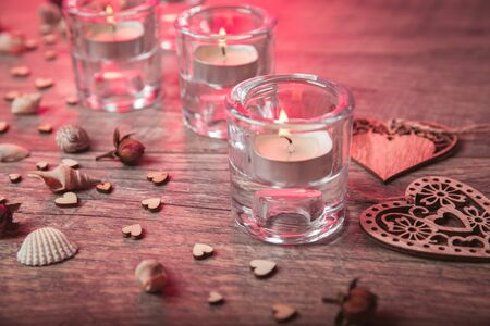 Spa concept in Valentines Day, candles, handmade heart, seashells, setting for aroma therapy and salt massage on bed, relax and healthy care. Rustic style. Toned image in chocolate, red, pink tones.