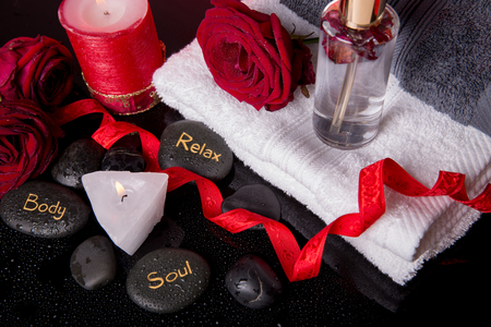 Spa concept in Valentines Day, red roses, candles in the shape of heart, spa stones with the inscription soul, body, relax