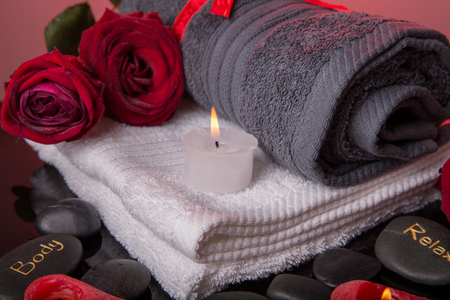 Spa concept in Valentine's Day, red roses, candles in the shape of heart, black therapy stones with the inscription soul, body, relax
