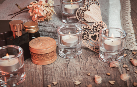 Spa concept in Valentines Day, candles, handmade heart, dry flowers, seashells, setting for aroma therapy and massage on bed, relax and healthy care. Rustic style. Toned image in chocolate, tones.