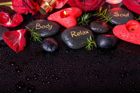 Spa concept in Valentines Day, red roses, candles in the shape of heart, black therapy stones with the inscription soul, body, relax Stock Photo