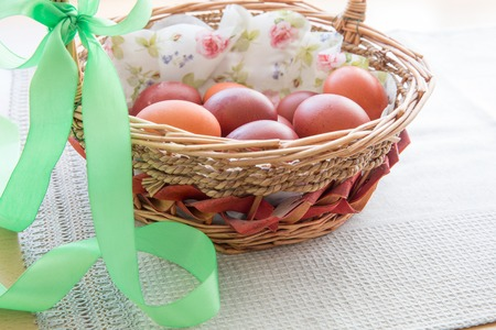 Easter eggs in the basket with green ribbon on a festive table near the window