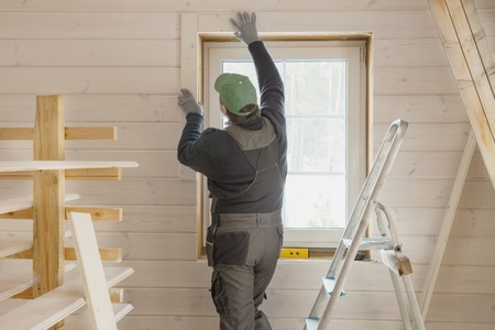 Construction worker thermally insulating eco wooden frame house with wood fiber plates. Latvia Banque d'images