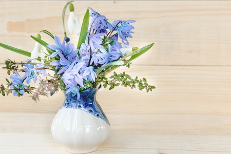 Bunch of spring flowers, small bouquet of tender spring flowers in vase. White and blue Snowdrop on wooden white background. Easter, Birthday, Mother's, Valentines, Women's, Wedding Day concept