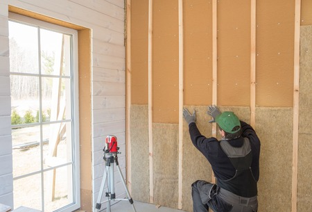 Construction worker thermally insulating eco-wood frame house with wood fiber plates and heat-isolating natural hemp material. Finishing the walls with a white wooden board, using laser line level. Banque d'images