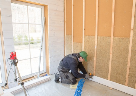 The worker makes finishing works of walls with a white wooden board, using laser line level. Building heat-insulating eco-wooden frame house with wood fiber plates Stock Photo
