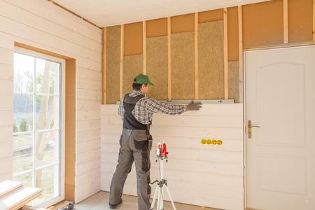 Der Arbeiter fertigt die Wandarbeiten mit einem weißen Holzbrett unter Verwendung einer Laserlinie an. Gebäude wärmeisolierendes Öko-Holzrahmenhaus mit Holzfaserplatten Standard-Bild