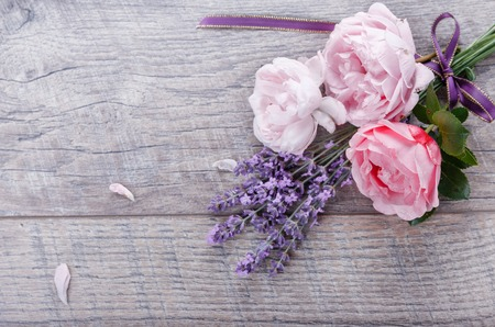 Festive flower English roses composition with ribbon, lavender on wooden background, rustic style. Overhead top view, flat lay. Copy space. Birthday, Mothers, Valentines, Womens, Wedding Day concept.