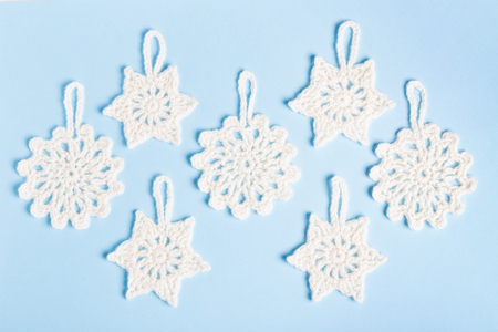 Christmas composition of crocheted white snowflakes and stars on blue background. Top view, flat lay, copy space.