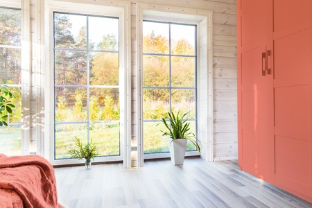 Bright interior, room in wooden house with large window. Scandinavian style. color of the year 2019 living coral 免版税图像