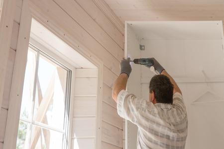 Le processus d'assemblage de meubles, le maître assemble une armoire blanche à l'aide d'une perceuse électrique dans une pièce avec une finition en bois blanc Banque d'images