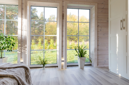 Bright interior, room in wooden house with large window. Scandinavian style. Фото со стока