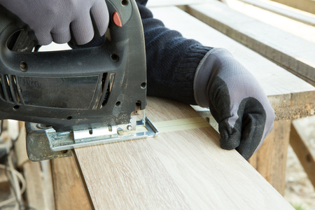 Man laying laminate flooring in construction concept. Construction, repair concept. 版權商用圖片
