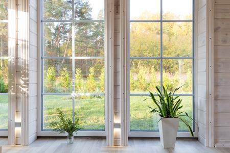 Interior de estudio fotográfico brillante con ventana grande, techo alto, piso de madera blanca