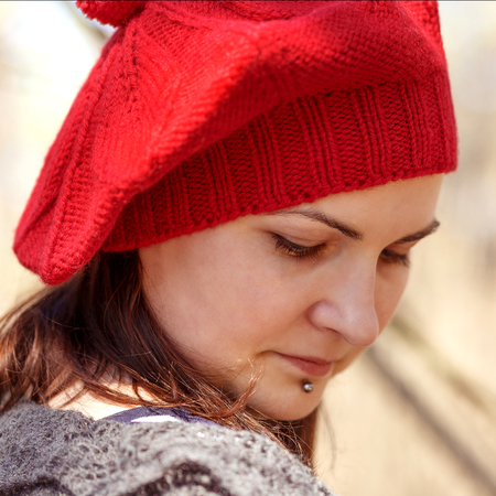 Outdoor close up portrait of young beautiful happy smiling girl wearing béret rouge de style français
