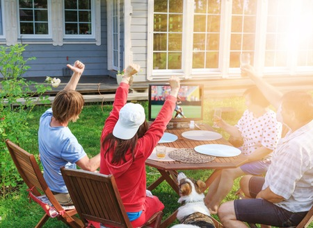 Happy family or company of friends watching football on TV in the courtyard of their home outdoors. Imagens