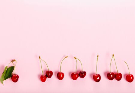 Tropical summer abstract background. Cherry cherries with cuttings and leaves on the pink background. Reklamní fotografie
