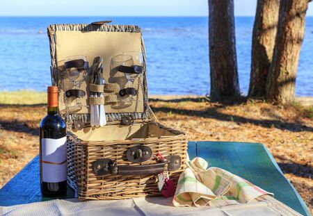 Picnic basket on the wooden table on the beach
