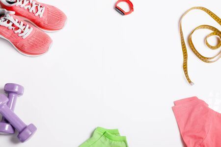 Fittnes sport composition with pink sneakers, t-shirt, dumbbells on white background.