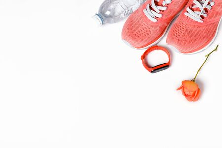 Fittnes sport composition with pink sneakers, smart bracelet on white background.