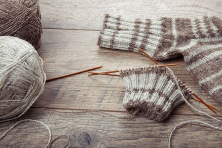 The process of knitting sock with circular bamboo knitting needles, on a wooden rustic table.
