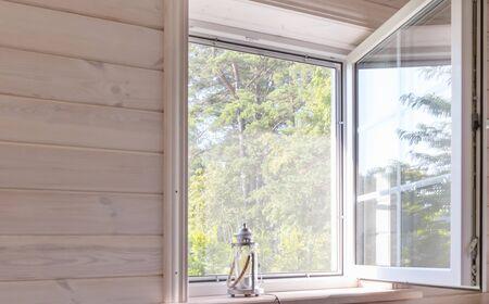 Weißes Fenster mit Moskitonetz in einem rustikalen Holzhaus mit Blick auf den Garten, geringe Schärfentiefe