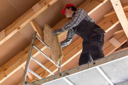 Trabajador de construcción que aísla térmicamente los hogares ecológicos del marco de madera del eco