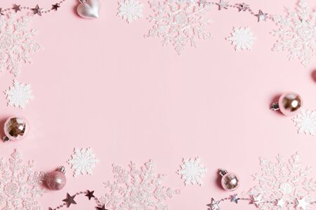 Christmas composition. Frame made of balls and snowflakes on pastel pink background.