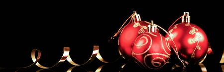 Christmas red ball with gold ribbon over black background