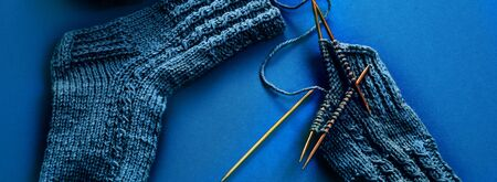 The process of knitting sock with circular bamboo knitting needles, woolen yarn of classic blue color on blue table. Color of the year 2020 classic blue Foto de archivo - 135881769