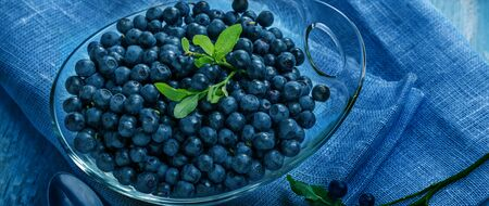 Freshly blueberries in glass bowl. Juicy and fresh blueberries with green leaves on blue wooden table. Concept for healthy eating and nutrition. Foto de archivo - 135976556